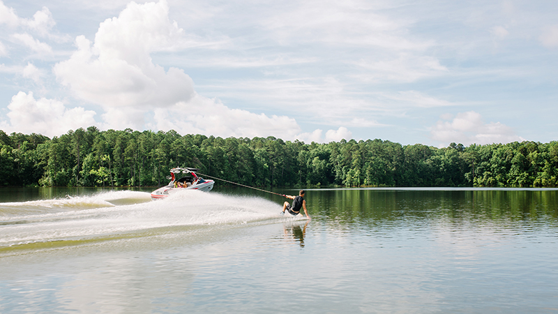 Wake boarder riding across a lake behind a speed boat on a lake.